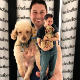 Man holding 3D printed figurine of him and his dog